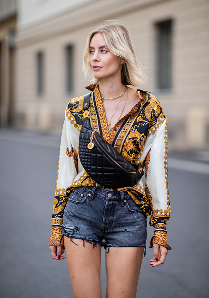 BERLIN, GERMANY - JULY 06: Lisa Hahnbueck wearing silk blouse with print Versace, Versace fanny belt bag , Levis 501 shorts, Tods loafer during the Berlin Fashion Week July 2018 on July 6, 2018 in Berlin, Germany. (Photo by Christian Vierig/Getty Images)